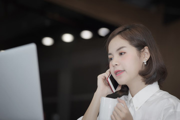 businesswoman holding cup of coffee and using smartphone while working
