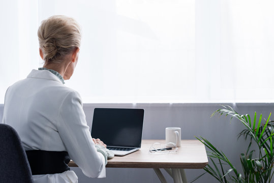 back view of senior businesswoman using laptop with blank screen in office