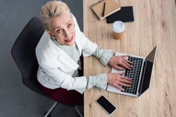 overhead view of elegant business woman working with laptop in modern office