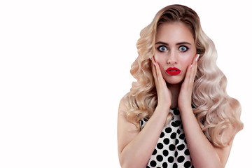 A woman with red bright lips suddenly touched her hands to her cheeks. A beautiful girl with curly hair is surprised and shocked. Presentation of your product. Expressive facial expressions