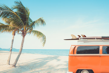 Wall Mural - vintage car parked on the tropical beach (seaside) with a surfboard on the roof - Leisure trip in the summer. retro color effect