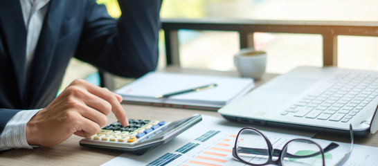 Businessman using calculator for analysis maketing plan, Accountant calculate financial report, computer with graph chart.  Business, Finance and Accounting concepts - fototapety na wymiar
