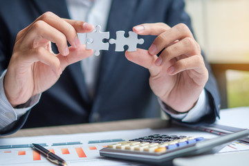 Businessman Hand connecting couple puzzle piece, Pen, Laptop, Calculator and Paperwork. Business solutions, target, successful, goals and strategy concepts