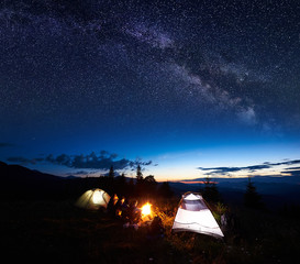 Family travellers, four persons resting at night camping in mountains, sitting on log beside campfire and two illuminated tents, enjoying beautiful view of evening sky full of stars, Milky way