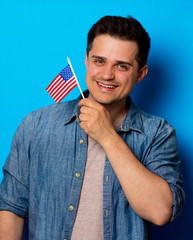 Young man in jeans shirt with an American flag on blue background