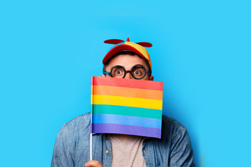 Young nerd man with noob hat holding a rainbow flag on blue background