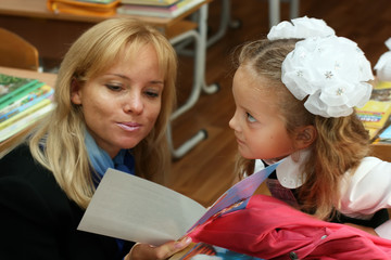 A beautiful young blonde reads a greeting postcard to a little schoolgirl with big white bows in the classroom