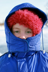 a little girl in a blue winter jacket and in hood in froozy winter day.