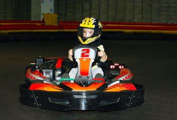 a the smiling little girl in a helmet in the go-kart on the karting track indoors