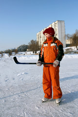 a smiling little girl in an orange overalls is standing on a skating rink in skates and holds a hockey stick in her hand