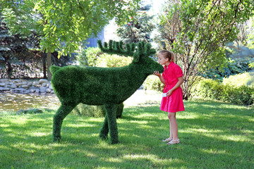 charming teen girl in a pink dress near the bush sculpture of a moose