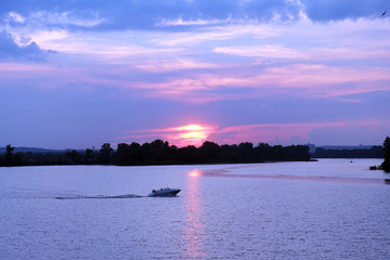 a motor boat sails on the river at sunset of the day