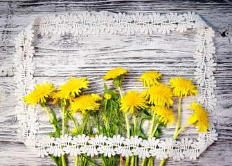 bouquet of wildflowers, dandelions and buttercups, in the style of a rustic postcard on a wooden background in a picture frame made of lace. copy space for your greeting text.
