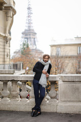 Afro american young man standing near concrete railing with Eiffel Tower background in Paris. Boy wearing grey scarf and black sweater. Concept of fashionable look and trip to France.