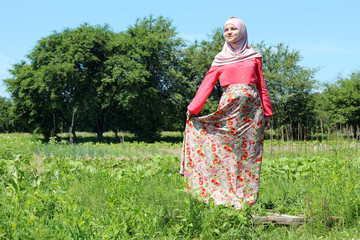 pregnant young woman in colorful muslim clothes is posing in front of camera in nature
