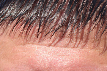 part of the forehead of a mature man with a short black fringe