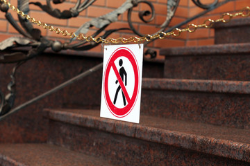 road sign prohibiting the movement of pedestrians is hanging on a chain above the stairs