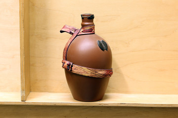 a brown opened bottle tied with a ribbon