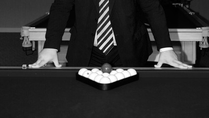 a man in a suit leans his hands on a pool table, on which there are billiard balls