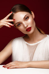 Beautiful girl in white dress with classic make-up and red manicure. Beauty face. Photo taken in the studio.