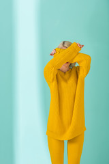 obscured view of woman in yellow sweater and tights posing on blue background