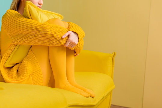 partial view of woman in yellow sweater and tights sitting on yellow sofa