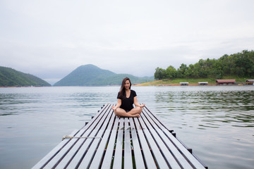 Portrait of a asian woman sitting on a wooden pier doing Yoga looking at the river
