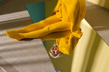 partial view of woman in yellow sweater and tights sitting on mirror with reflection in it