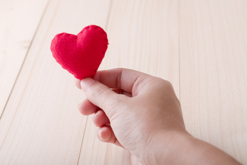 Giving a Red Heart on Wood Background