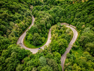 Extreme winding highway in the mountains passing trough a forest. Aerial view.