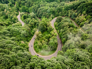 Aerial view of a curved road in the forest shot with a drone
