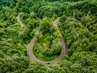 Car passing on an extreme winding road in the forest, aerial view