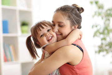 love and family concept - happy mother and child daughter hugging at home