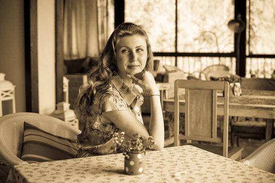 Woman in vintage dress, 1950s style interior, retro style in modern life, pretty girl look nice and rest on weekend in kitchen