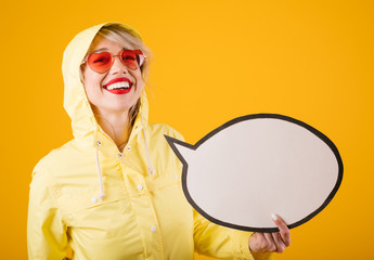 Smiling woman in yellow raincoat. Funny girl on yellow background holding speech buble empty copyspace you can place your text information. Ad template