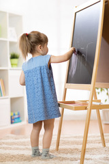 Child girl painting at easel in school.