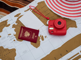 Passport, instant camera, female hat and blank sheet of paper on an old map. Adventure and travel