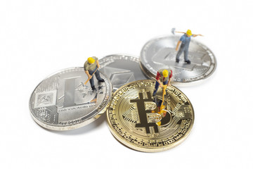 Miniature Workers Mining Various Cryptocurrencies On A White Surface