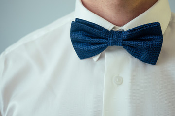 beautiful blue tie butterfly on the white shirt of the groom