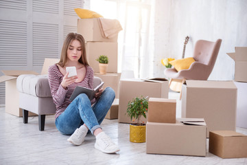 Need assistance. Charming young woman sitting on the floor and checking the number of removers company before moving out of the house