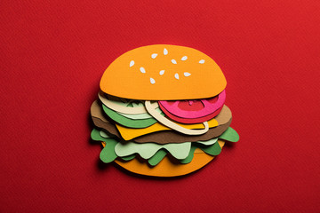 Creative art conceptual collage with space for text. Stylized craft paper burger a red background. Composition cut out from colored paper. Illustrative picture.