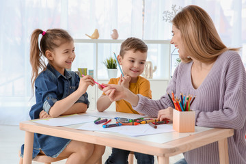 Cute little children and their nanny drawing at home