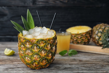 Pineapple with juice and ice cubes on table