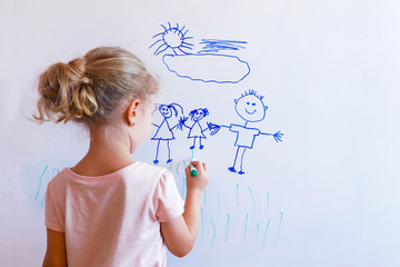 Little girl draws family on a white board.