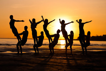 Silhouettes against the sunset are engaged in sports, fitness, yoga. A group of people.