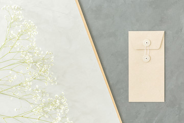 A minimalist geometrical arrangement with small white flowers and an envelope on light and dark gray backgrounds