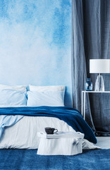 Blue watercolor paint on the wall in modern bedroom interior with a double bed and grey curtain