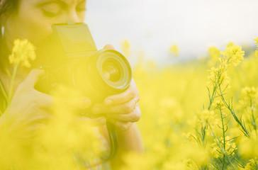crop woman taking picture in field