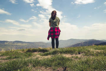 Young girl stands with her back on top of the mountain