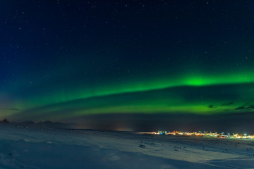 Northern lights over town of Hauganes in Iceland
